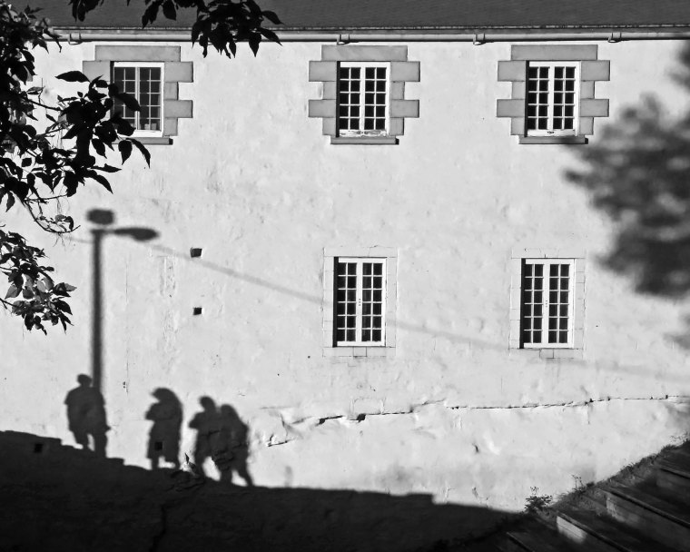 The last light of early evening casts shadows on an old building of four young people under a street light.
